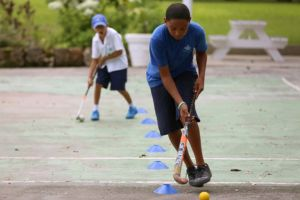 Students playing field hockey at Codrington School in Barbados